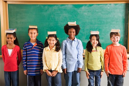 Row of students with books on their heads in classroom Stock Photo - Premium Royalty-Free, Code: 673-02141922
