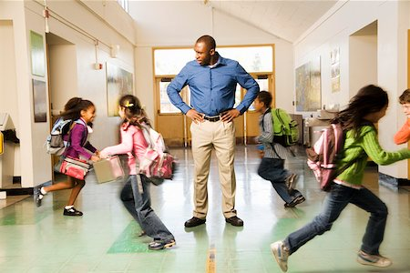 Blurred motion shot of students running past teacher Stock Photo - Premium Royalty-Free, Code: 673-02141944