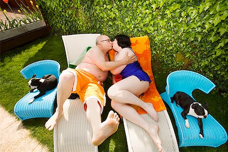 Couple kissing on lawn chairs in backyard Stock Photo - Premium Royalty-Free, Code: 673-02142337