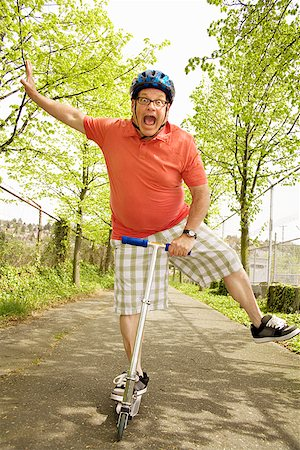 fat man exercising - Clumsy man riding a scooter Stock Photo - Premium Royalty-Free, Code: 673-02142347