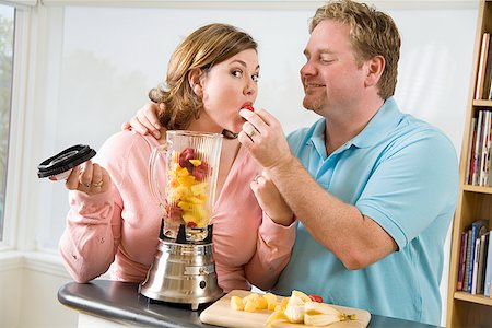 Couple eating fruit while making a smoothie Stock Photo - Premium Royalty-Free, Code: 673-02142412