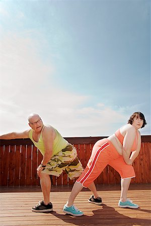 fat man exercising - Couple stretching on patio Stock Photo - Premium Royalty-Free, Code: 673-02142459