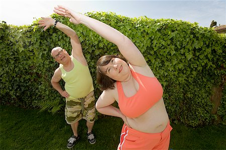 fat man exercising - Couple stretching in backyard Stock Photo - Premium Royalty-Free, Code: 673-02142460