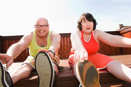 fat man exercising - Couple stretching on patio Stock Photo - Premium Royalty-Free, Code: 673-02142462