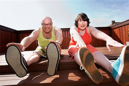 fat man exercising - Couple stretching on patio Stock Photo - Premium Royalty-Free, Code: 673-02142463