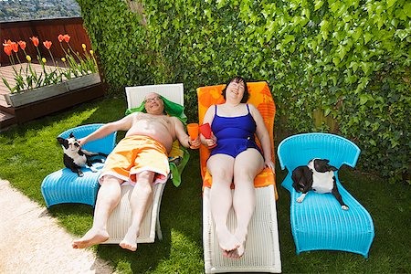 dog in heat - Couple relaxing on lawn chairs in backyard Stock Photo - Premium Royalty-Free, Code: 673-02142471