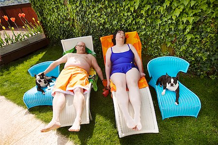 dog in heat - Couple relaxing on lawn chairs in backyard Stock Photo - Premium Royalty-Free, Code: 673-02142472