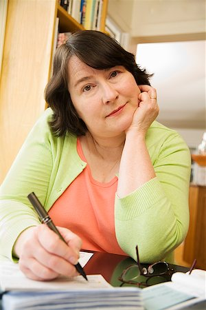 Woman writing a check Stock Photo - Premium Royalty-Free, Code: 673-02142513