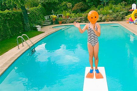 Girl with balloon in front of face over swimming pool Stock Photo - Premium Royalty-Free, Code: 673-02142844
