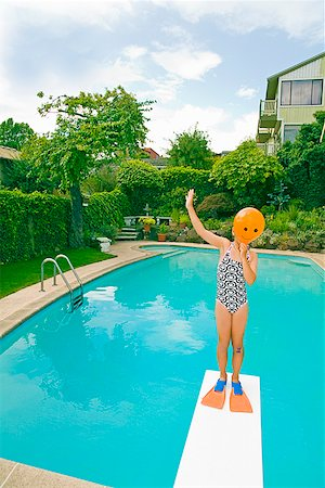 Girl with balloon in front of face over swimming pool Stock Photo - Premium Royalty-Free, Code: 673-02142845