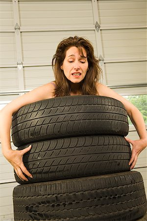 Nude woman standing in stack of tires Stock Photo - Premium Royalty-Free, Code: 673-02142840