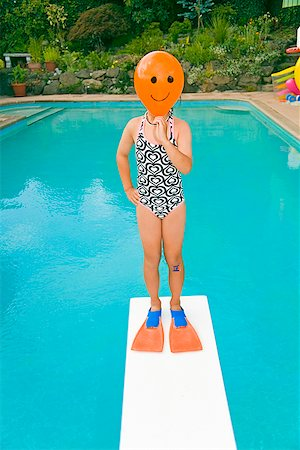 Girl with balloon in front of face over swimming pool Stock Photo - Premium Royalty-Free, Code: 673-02142843