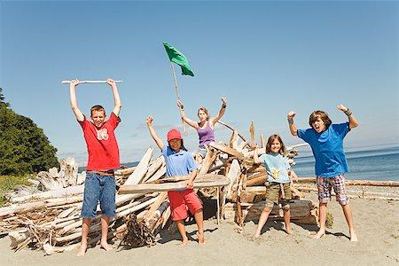 Children cheering next to beach fort Stock Photo - Premium Royalty-Free, Code: 673-02142878