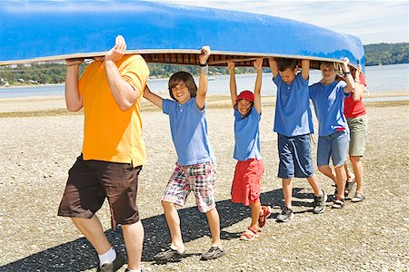 Male camp counselor and children carrying canoe Stock Photo - Premium Royalty-Free, Code: 673-02142943