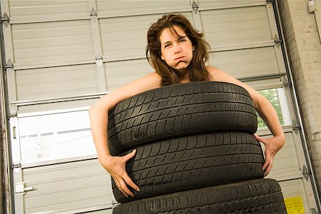 Nude woman standing in stack of tires Stock Photo - Premium Royalty-Free, Code: 673-02143194