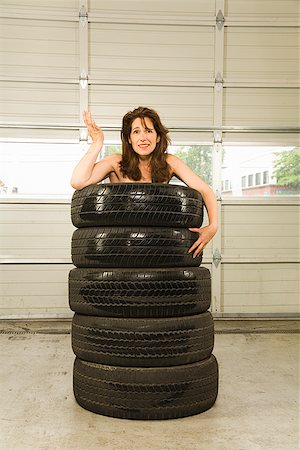 Nude woman standing in stack of tires Stock Photo - Premium Royalty-Free, Code: 673-02143193