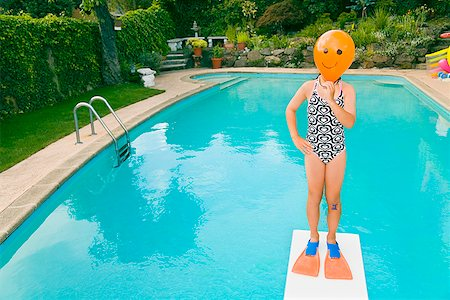 Girl with balloon in front of face over swimming pool Stock Photo - Premium Royalty-Free, Code: 673-02143227