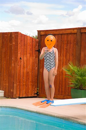 Girl with balloon in front of face over swimming pool Stock Photo - Premium Royalty-Free, Code: 673-02143229