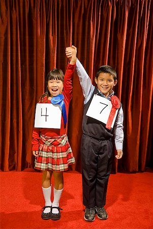 Asian girl and boy wearing prize ribbons on stage Stock Photo - Premium Royalty-Free, Code: 673-02143370