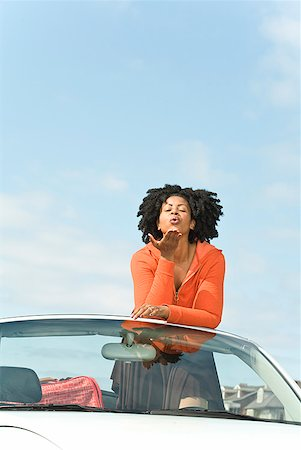 African woman blowing kiss in convertible car Stock Photo - Premium Royalty-Free, Code: 673-02143414