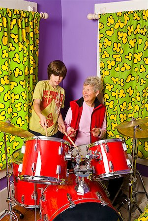 Boy showing grandmother how to play drums Stock Photo - Premium Royalty-Free, Code: 673-02143544