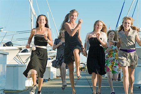 Group of teenaged girls running at marina Stock Photo - Premium Royalty-Free, Code: 673-02143600