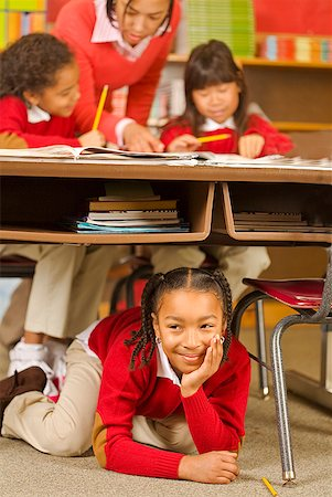 photo of class with misbehaving kids - African girl sitting under school desk Stock Photo - Premium Royalty-Free, Code: 673-02143686