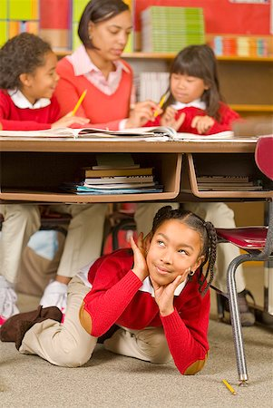 photo of class with misbehaving kids - African girl sitting under school desk Stock Photo - Premium Royalty-Free, Code: 673-02143687