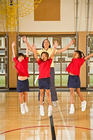 Multi-ethnic girls and teacher jumping in school gym Stock Photo - Premium Royalty-Free, Code: 673-02143708
