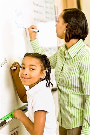 African teacher and student writing on whiteboard Stock Photo - Premium Royalty-Free, Code: 673-02143736