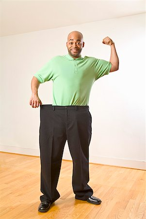 skinny man muscle pose - African man holding out waistband of big pants Stock Photo - Premium Royalty-Free, Code: 673-02143790