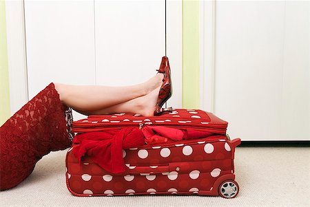 Woman in red dress resting on polka dot patterned suitcase Stock Photo - Premium Royalty-Free, Code: 673-02216480