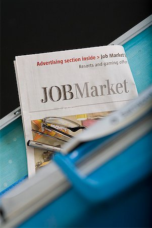 Briefcase, eyeglasses and employment section of newspaper Stock Photo - Premium Royalty-Free, Code: 673-02216499
