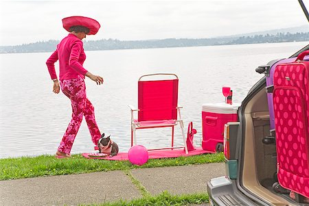 Woman in pink and Boston Terrier dog picnicking by bay Stock Photo - Premium Royalty-Free, Code: 673-02216534