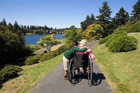 Girl assisting a disabled woman in a wheelchair Stock Photo - Premium Royalty-Free, Code: 673-02386529