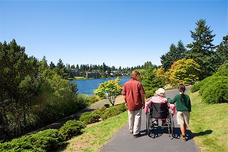 Man with a girl assisting a woman in a wheelchair Stock Photo - Premium Royalty-Free, Code: 673-02386539