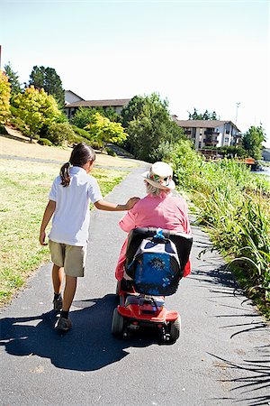 Girl walking with her grandmother sitting in a wheelchair Stock Photo - Premium Royalty-Free, Code: 673-02386550
