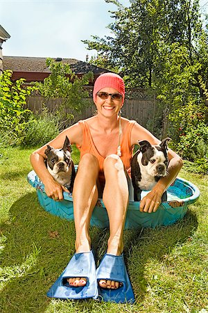 dog in heat - Woman sitting in a wading pool with two Boston Terriers Stock Photo - Premium Royalty-Free, Code: 673-02386604