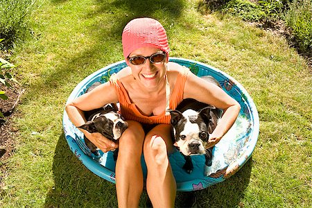 dog in heat - Woman sitting in a wading pool with two Boston Terriers Stock Photo - Premium Royalty-Free, Code: 673-02386605