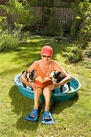 dog in heat - Woman reading a book in a wading pool between two Boston Terriers Stock Photo - Premium Royalty-Free, Code: 673-02386606