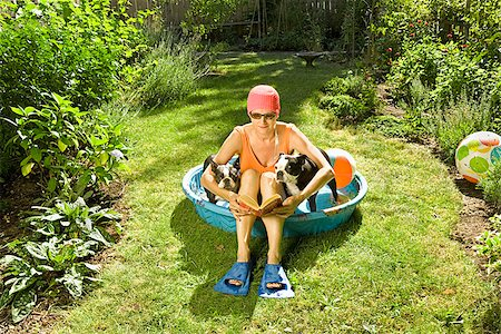 dog in heat - Woman reading a book in a wading pool between two Boston Terriers Stock Photo - Premium Royalty-Free, Code: 673-02386607