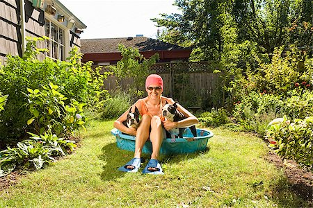 dog in heat - Woman sitting between two Boston Terriers in a wading pool Stock Photo - Premium Royalty-Free, Code: 673-02386608