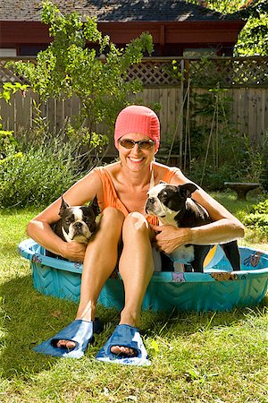 dog in heat - Woman sitting between two Boston Terriers in a wading pool Stock Photo - Premium Royalty-Free, Code: 673-02386609