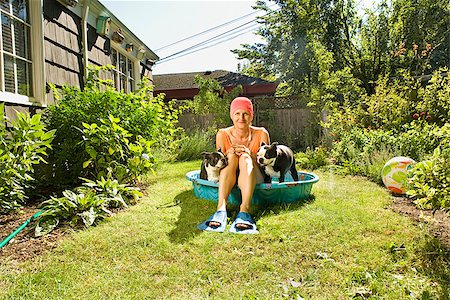 dog in heat - Woman sitting between two Boston Terriers in a wading pool Stock Photo - Premium Royalty-Free, Code: 673-02386611