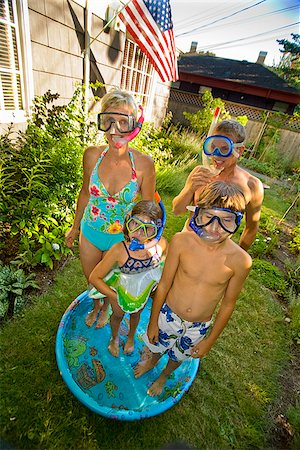 Family wearing snorkels and standing in a wading pool Stock Photo - Premium Royalty-Free, Code: 673-02386676
