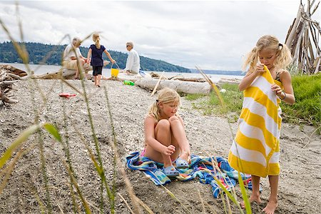 Two girls with their family on the beach Stock Photo - Premium Royalty-Free, Code: 673-02386673