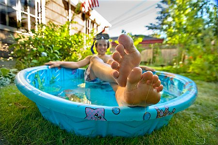 Boy wearing snorkel and lying in a wading pool Stock Photo - Premium Royalty-Free, Code: 673-02386687