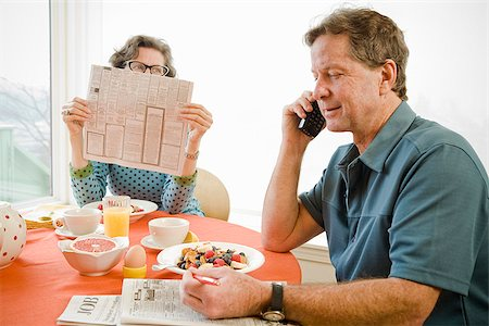Couple having breakfast and checking newspaper classifieds Stock Photo - Premium Royalty-Free, Code: 673-02801254