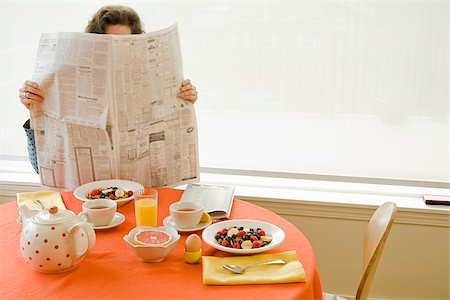Woman at home having breakfast and reading newspaper Stock Photo - Premium Royalty-Free, Code: 673-02801251
