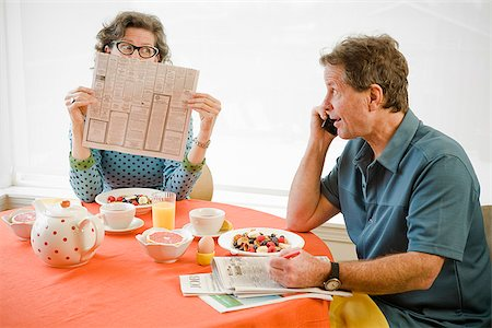 Couple having breakfast and checking newspaper classifieds Stock Photo - Premium Royalty-Free, Code: 673-02801253